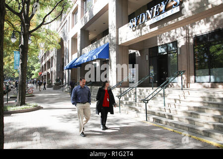 CHARLOTTE, NC, USA-10/31/18: A man and woman talk and stroll down Tryon at lunch hour on a sunny autumn day. - Stock Image