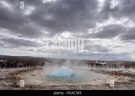 The famous geyser of Geysir, Iceland at the start of an eruption under a brooding sky - Stock Image