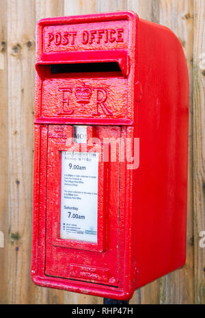 Close up of a red polemounted post box showing collection times by a wooden fence Wallasey Village February 2019 - Stock Image