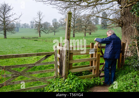 A man passes through a kissing gate to walk along a public footpath through green fields beyond through the Shropshire countryside near Worfield. - Stock Image