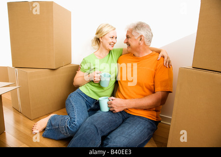Middle aged couple sitting on floor among cardboard moving boxes drinking coffee - Stock Image