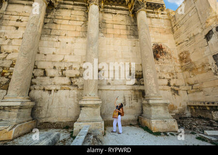 A young woman aims her camera at the ancient Hadrian's Library wall in the Roman Agora at Athens, Greece. - Stock Image