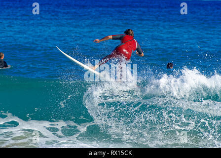 Surfer in red wet suit surfing on the crest of wave in mediterranean sea. - Stock Image