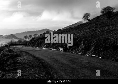 Mountain road with mist filling a valley in the background - Stock Image