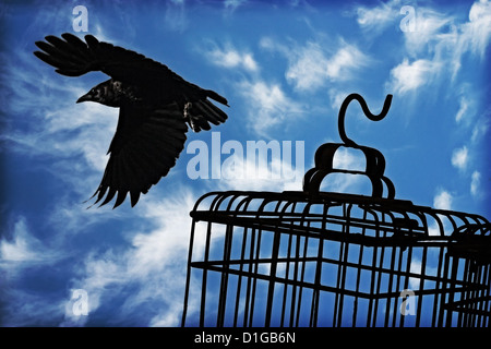A crow flies free, the cloudy sky in the background, a silhouetted cage in the foreground. - Stock Image