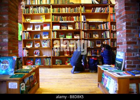 Family perusing shelves of bookstore, Burlington, VT, USA - Stock Image