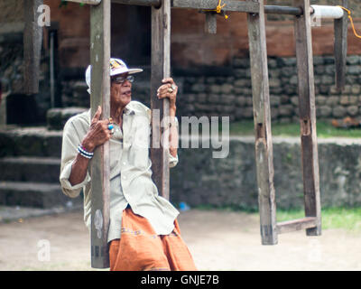 Old man just swinging in Tenganan Village- Bali - Stock Image