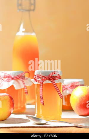 Homemade apple juice in a glass bottle and jelly in jars with linen cover and a nostalgic ribbon bow in bright sunshine in front of an apricot colored background. - Stock Image