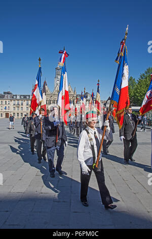 Men marching with raised banners and flags for Victory In Europe VE day 8th May 2018 in Place de l'Hotel de Ville St Quentin, Aisne, France. - Stock Image