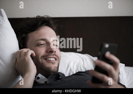 Man reclining in bed talking on phone and looking at second smart phone - Stock Image