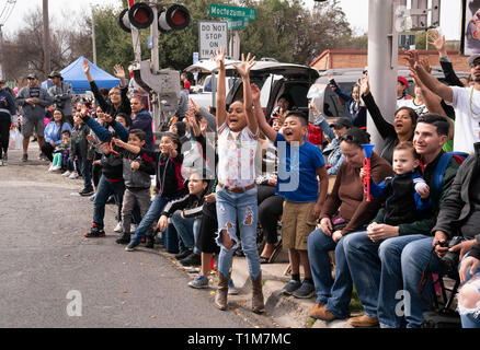 Kids yell and wave to riders on float asking for trinkets during annual Washington's Birthday Celebration parade in Laredo TX. - Stock Image