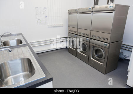 Communal Laundry room with washing machines and tumble dryers. - Stock Image