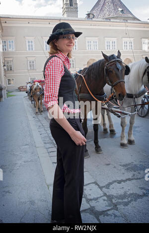 Portrait of a young Austrian woman who drives horse-drawn carriage tours of Salzburg, Austria. - Stock Image