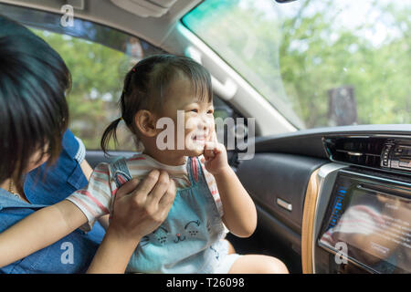 Asian kid girl is happiness in the car, family travel concept. - Stock Image