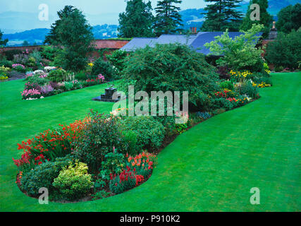 Aerial view of colourful flower island beds in lawn of a country house - Stock Image