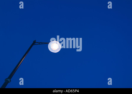 Street light on while it is still light ie wasting electricity - Stock Image