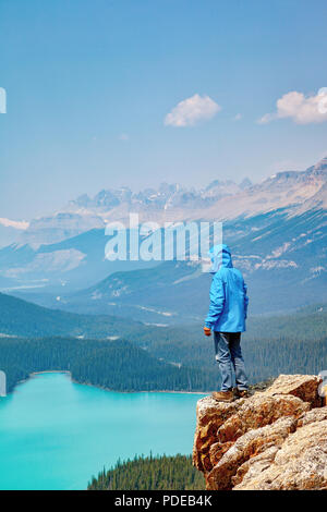 A hiker standing on the edge of Bow Summit overlooking Peyto Lake in Banff National Park on the Icefields Parkway. The glacier-fed lake is famous for  - Stock Image