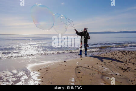 Bournemouth, UK. Sunday 3rd February 2019. A lady makes large bubbles on the beach in Bournemouth in Dorset, on a sunny winters day. Credit: Thomas Faull/Alamy Live News - Stock Image