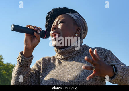 London, UK. 10th October 2018. Dr. Shola Mos-Shogbamimu speaks at the Shoulder to Shoulder rally in Hyde Park by groups campaigning for women born in the 1950s to regain the pensions stolen from them under successive governments, including The Waspi Campaign (Women Against State Pension Inequality),  Back to 60, We Paid In, You Pay Out and others. Credit: Peter Marshall/Alamy Live News - Stock Image
