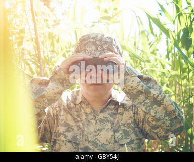 A soldier man is looking through binoculars in the woods outside with a uniform on for a protection, war or hunter - Stock Image