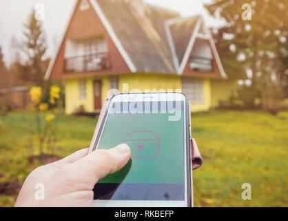 Person hand press lock/unlock button from distance on smartphone app to open/close rural home house door. Modern lifestyle technology concept. - Stock Image