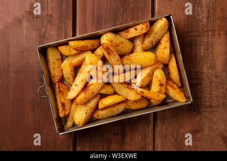 Potato wedges, oven roasted, shot from the top in a baking tray on a dark rustic wooden background - Stock Image