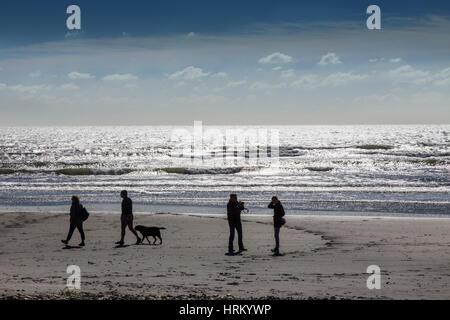 Beach walkers, south coast of England. - Stock Image