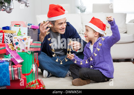 Father And Daughter Holding Christmas Ornaments - Stock Image