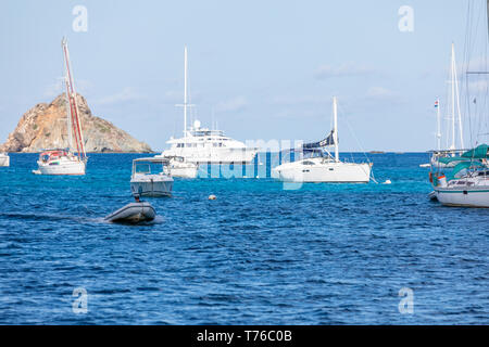 A person operating a small dinghy near larger boats in the port of Gustavia in St Barts - Stock Image