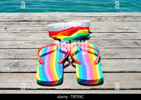 closeup of a pair of rainbow-patterned flip-flops and a rainbow-patterned swimsuit on a weathered dock, next to the ocean or a pond - Stock Image