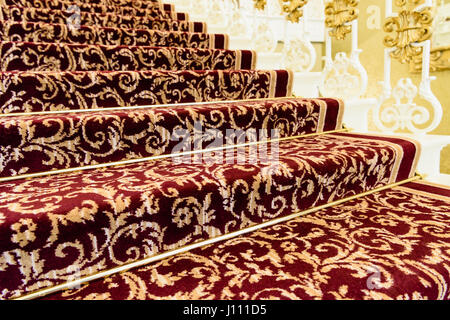 Brass stairrods holding down red patterened Axminster carpet on the stairs of a posh house. - Stock Image