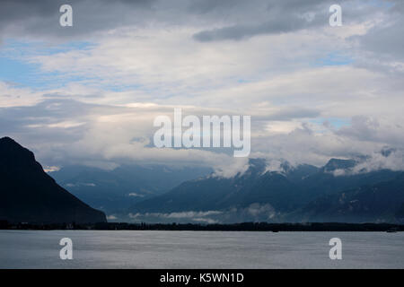 Low clouds at the end of the day with some blue sky at the base of the Alps mountains and over the freshwater of - Stock Image