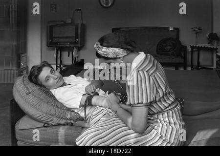 woman laying down on a couch preparing to have an injection in her arm by another lady 1930s hungary - Stock Image