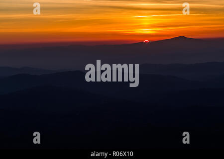 Beautiful sunset with sun coming down behind various layers of mountains - Stock Image