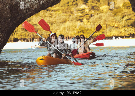 Group of happy friends walks by kayaks under big rocks in the sea. Kayaking or canoeing travel photo with group of peoples - Stock Image