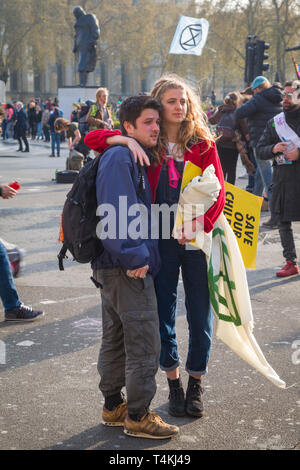 A young couple with a 'Save our Children' banner by Parliament Square, Westminster for the Extinction Rebellion demonstration - Stock Image