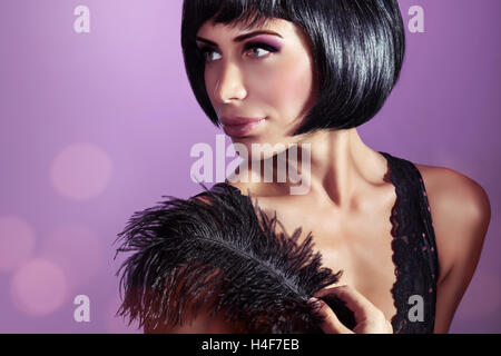 Portrait of an attractive stylish model posing with black feather over purple background, stylish bob haircut and - Stock Image