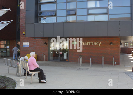 Elderly people sitting out side the pharmacy next to the Pallion Health Centre. - Stock Image