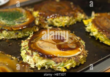 Okonomiyaki cooking on a hot plate. - Stock Image