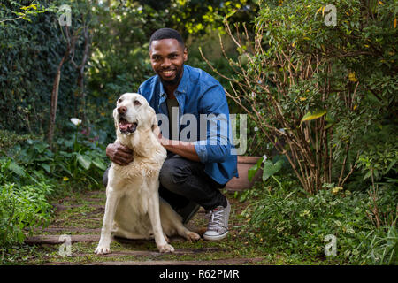 A man petting his dog - Stock Image