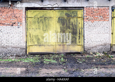 Old yellow painted metal door in a vintage grunge style composition. - Stock Image
