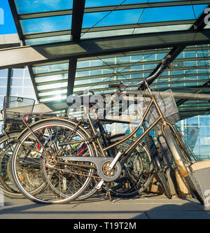 Closeup of bicycles on parking by Kastrup International airport under glass canopy in sunshine day, Copenhagen, Denmark - Stock Image