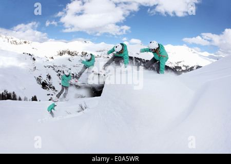 Multi exposure of young woman snowboarding on mountain, Mayrhofen, Tyrol, Austria - Stock Image