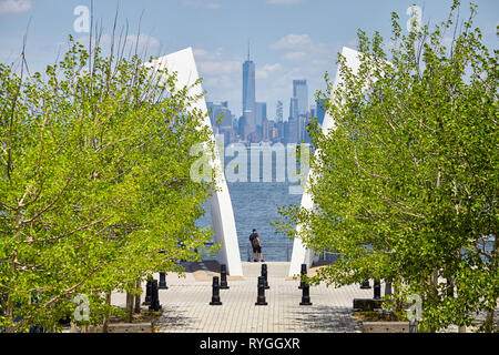 New York, USA - June 29, 2018: Man stands between Postcards, Staten Island September 11 Memorial with Manhattan in distance. - Stock Image