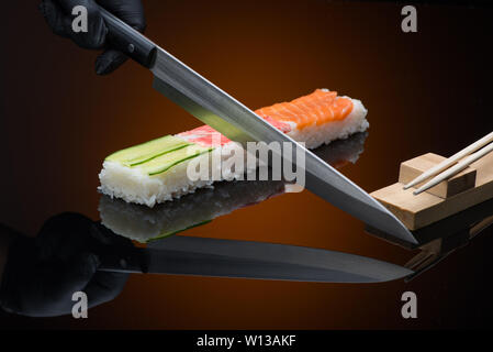 chef prepares sushi, cuts with a knife. sushi on red  background with reflection - Stock Image
