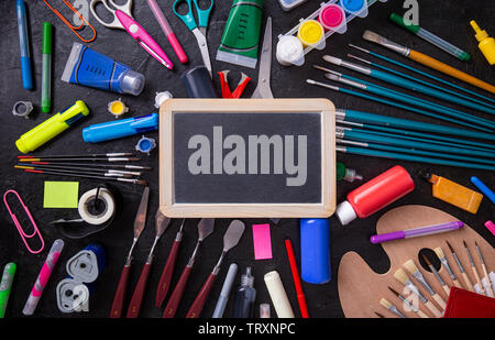 Small blackboard and various stationery. Back to school concept - Stock Image