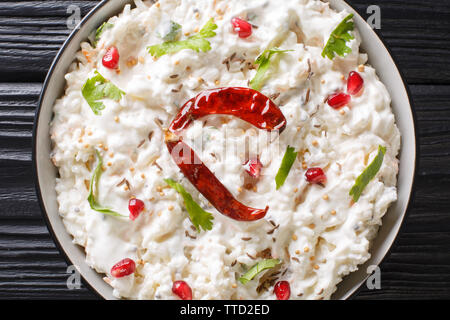 Indian Curd rice with carrots, pomegranate and with additional tempering of spices close-up in a plate on the table. horizontal top view from above - Stock Image