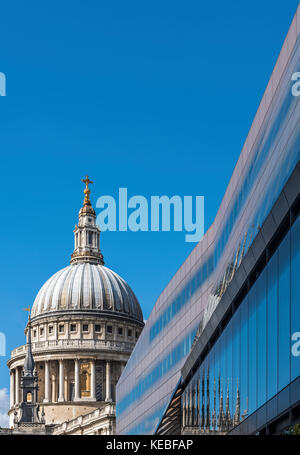 The ornate dome of St Paul's Cathedral set against modern architecture - Stock Image