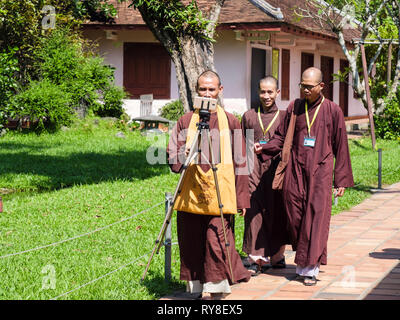 Monks walking and taking a selfie on a mobile phone at Thien Mu Pagoda complex. Hue, Thừa Thien–Hue Province, Vietnam, Asia - Stock Image