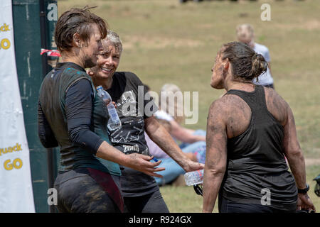 Muddy happy women having completed a mud run - Stock Image